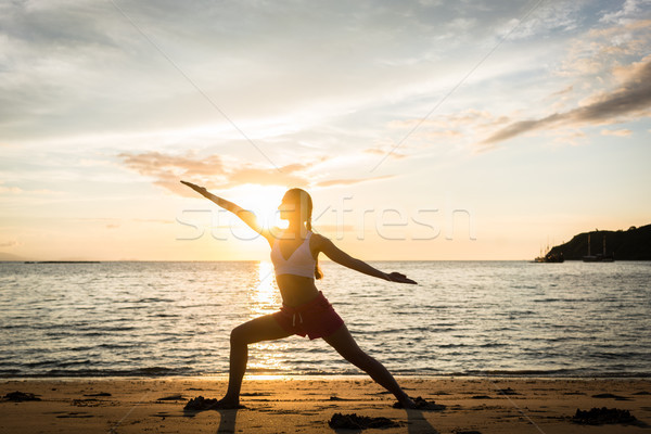 Silhouette of a fit woman practicing the warrior yoga pose at sunset Stock photo © Kzenon