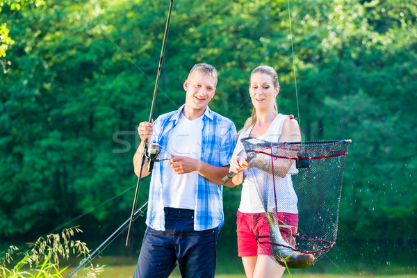 Couple sport fishing bragging with fish caught  Stock photo © Kzenon