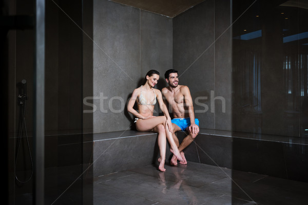 Young couple in love sitting in the steam bath of a modern spa center Stock photo © Kzenon