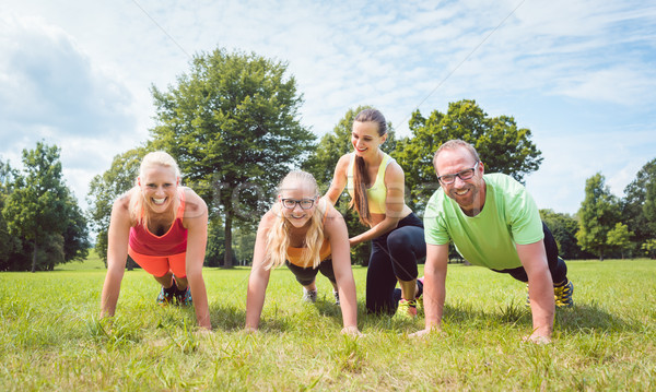 Family doing push-ups in nature under guidance by a fitness coach Stock photo © Kzenon