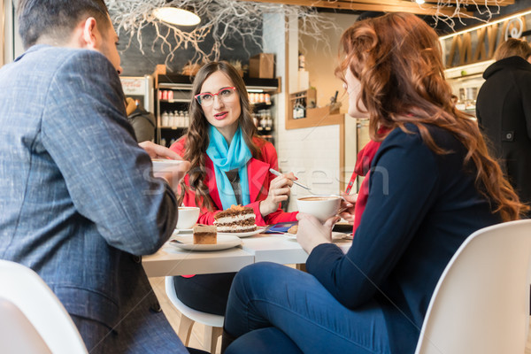 Three young colleagues relaxing during coffee break in a trendy cafeteria Stock photo © Kzenon