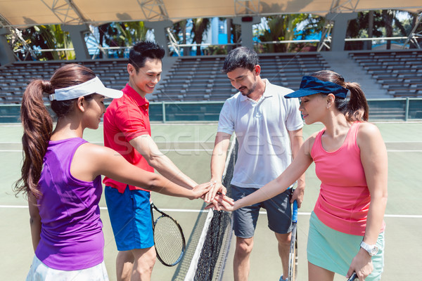 Four young tennis players putting hands together before a doubles mixed match  Stock photo © Kzenon