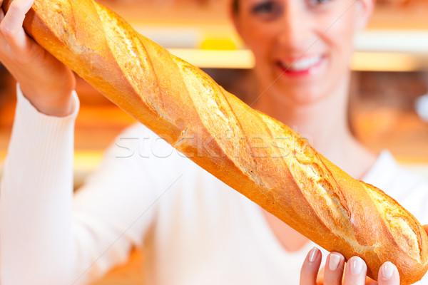 Female baker in her bakery with baguette Stock photo © Kzenon