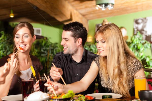 Jeunes manger thai restaurant baguettes femme Photo stock © Kzenon