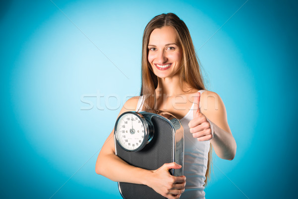 Losing weight - Young woman with measuring scale Stock photo © Kzenon