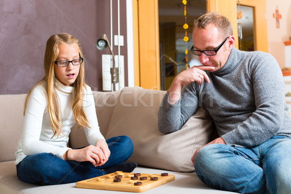 Stock photo: Father and daughter playing checkers