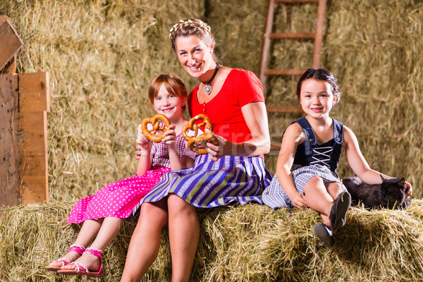 Bavarian family sitting on hayloft with pretzels Stock photo © Kzenon