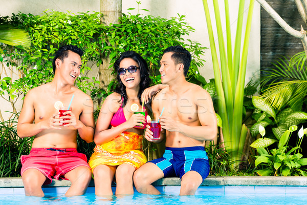 Asian friends drinking cocktails at pool Stock photo © Kzenon
