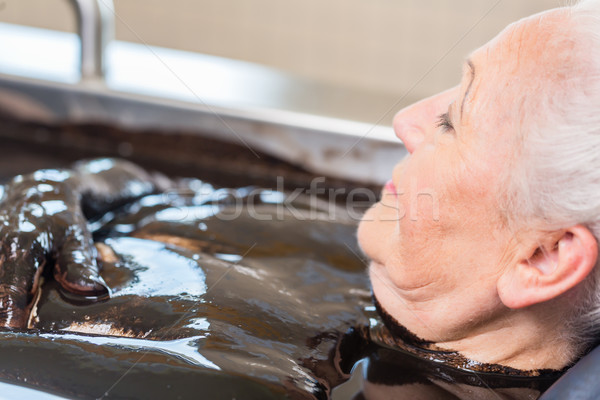 Senior woman enjoying mud bath alternative therapy Stock photo © Kzenon