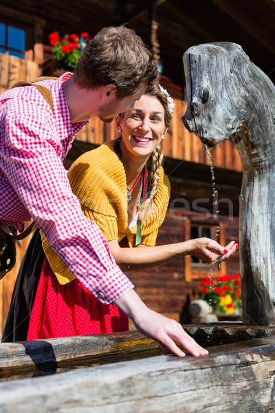 Couple at mountain hut drinking water from source Stock photo © Kzenon