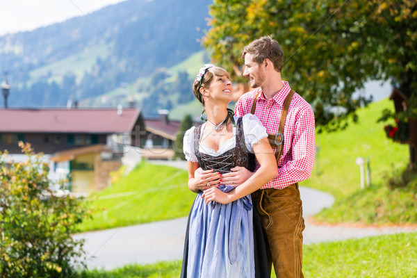 Couple in Tracht standing on meadow in alp mountains Stock photo © Kzenon
