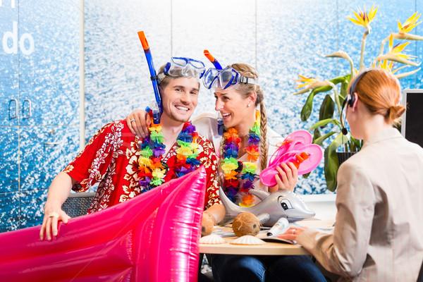 Man and woman booking beach holiday Stock photo © Kzenon