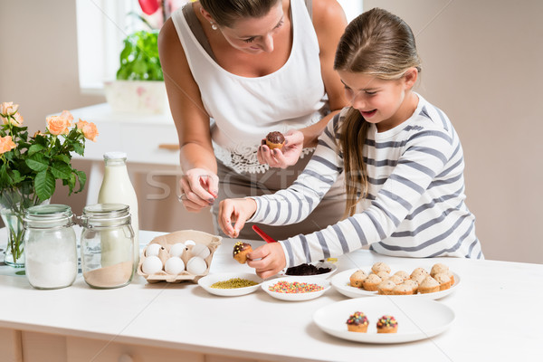 Pregnant mum and her little daughter baking together Stock photo © Kzenon