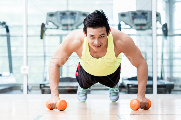 Bodybuilder doing pushups holding dumbbells in hands Stock photo © Kzenon