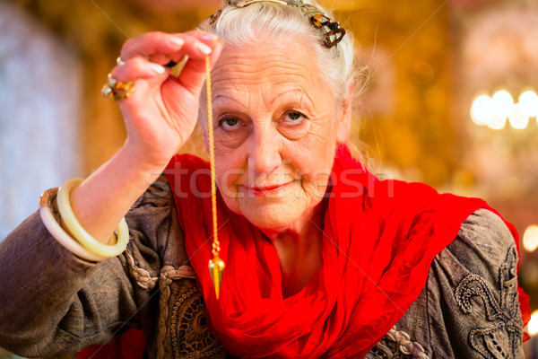 Fortuneteller in Seance with pendulum Stock photo © Kzenon