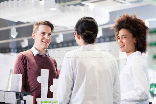 Happy customer talking with two helpful pharmacists in a contemporary drugstore Stock photo © Kzenon