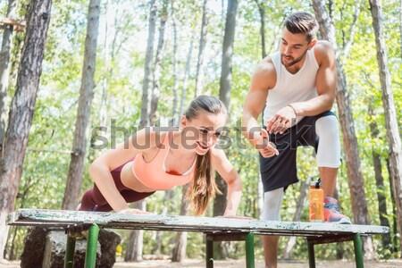 Beautiful woman doing a plank with man watching Stock photo © Kzenon