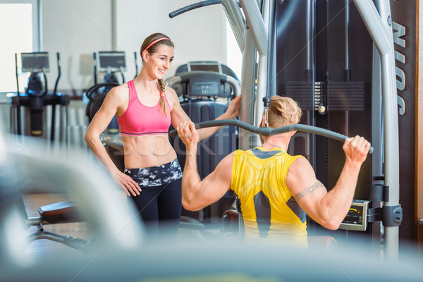 Fit beautiful woman smiling with admiration at a strong man in the gym Stock photo © Kzenon