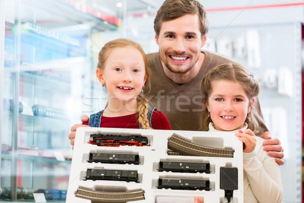 Family buying model railroad in toy store Stock photo © Kzenon