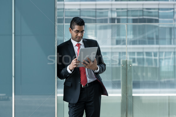 Indian businessman using a tablet PC indoors Stock photo © Kzenon