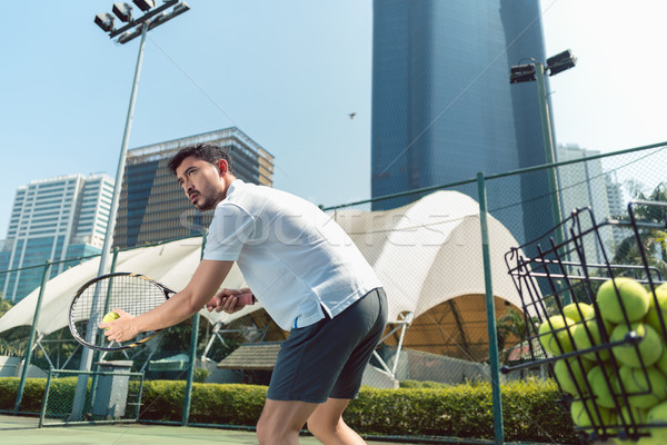 Young man playing tennis outdoors in a modern district of the city Stock photo © Kzenon