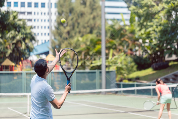 Rear view of a man ready to serve during doubles match Stock photo © Kzenon