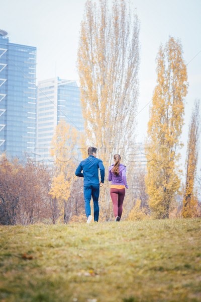 Couple seen from behind running thru a city in fall Stock photo © Kzenon