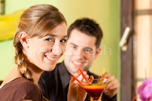 Young couple drinking cocktails in bar or restaurant Stock photo © Kzenon
