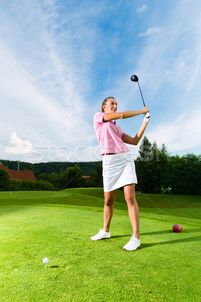 Young female golf player on course doing golf swing Stock photo © Kzenon