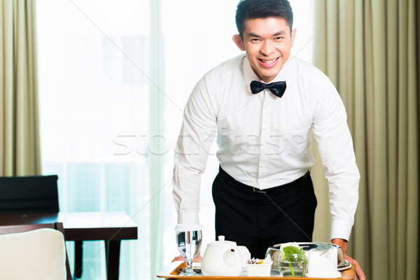 Asian Chinese room waiter serving guests food in hotel Stock photo © Kzenon