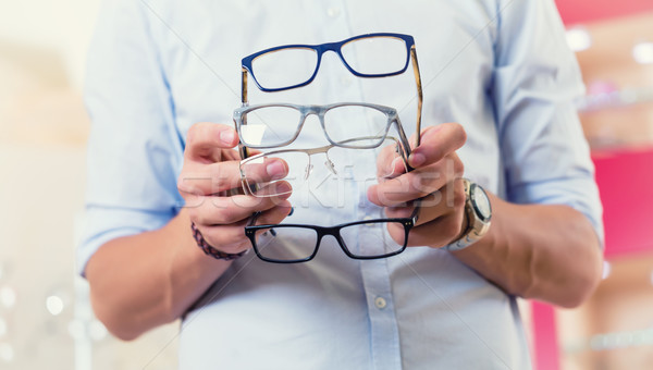 Man at optician or optometrist buying glasses Stock photo © Kzenon