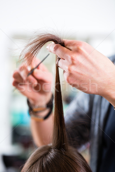 Male hairdresser cutting woman hair in hairdresser shop Stock photo © Kzenon