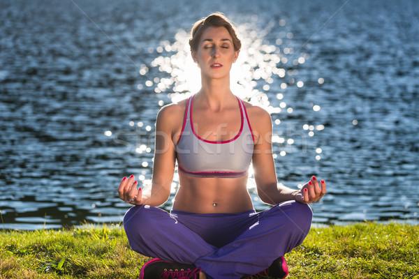 Woman doing yoga on lake Stock photo © Kzenon