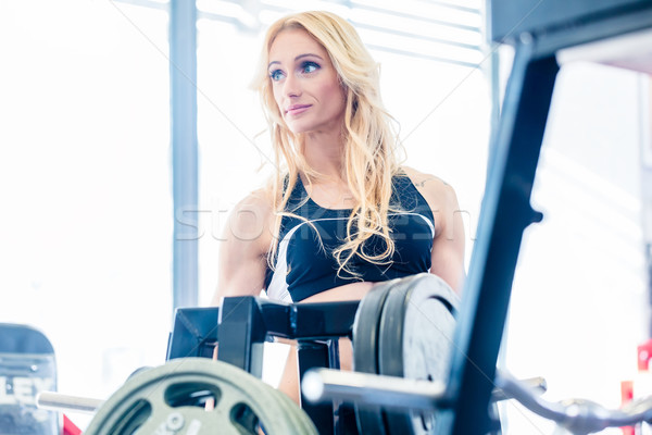 Woman taking weights from stand in fitness gym Stock photo © Kzenon