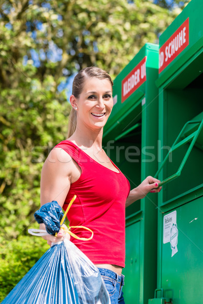Stock photo: Woman at clothes recycling skip