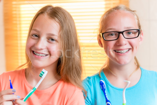 Two girls with dental retainers brushing teeth Stock photo © Kzenon