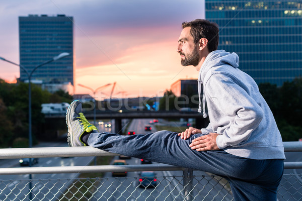 Runner stretching in front of office building at sunset Stock photo © Kzenon