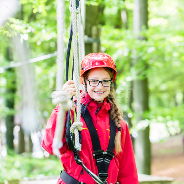 Girl roping up in high rope course Stock photo © Kzenon