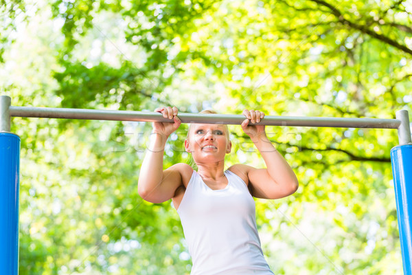 Woman exercising at high bar for better outdoor fitness Stock photo © Kzenon