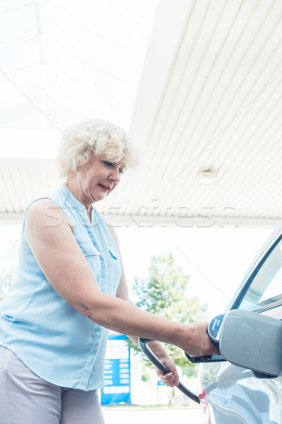 Active senior woman smiling while filling up the gas tank of her Stock photo © Kzenon