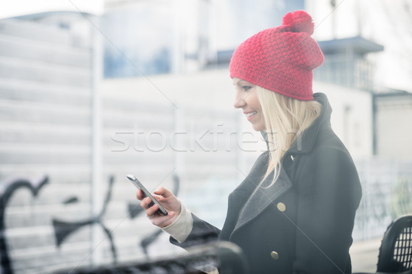 Woman using phone while waiting for a suburban train Stock photo © Kzenon