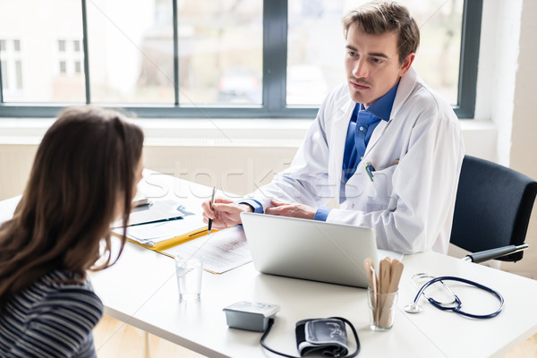 Young physician listening to his patient with respect and dedication Stock photo © Kzenon
