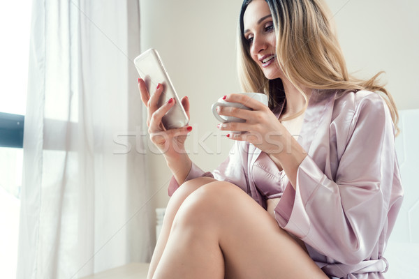 Woman checking her phone in the morning for messages Stock photo © Kzenon