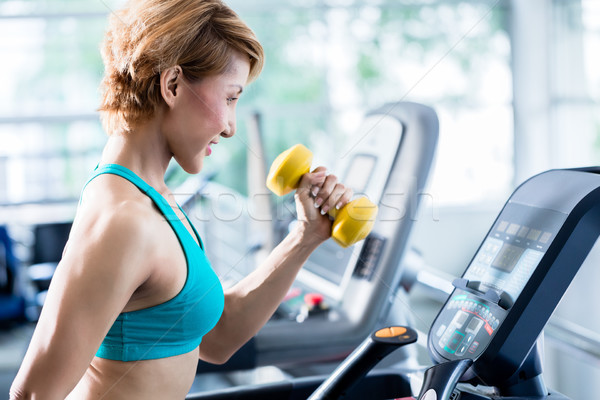 Asian woman walking on treadmill holding dumbbell Stock photo © Kzenon