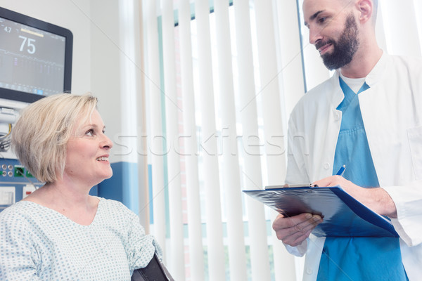 Doctor talking to patient in recovery room of hospital Stock photo © Kzenon