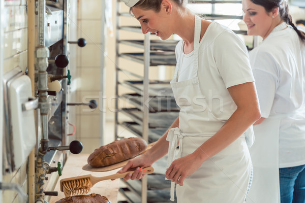 Team of two bakers preparing and coating bread Stock photo © Kzenon