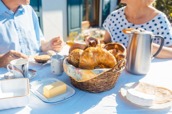 Two senior people having breakfast with bread basket on table in summer garden Stock photo © Kzenon