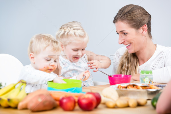 Portrait of a happy mother of two children sitting at table Stock photo © Kzenon