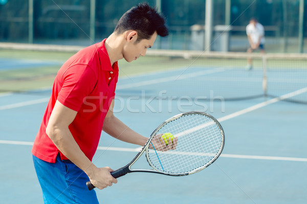 Asian tennis player looking at the ball with concentration before serving Stock photo © Kzenon