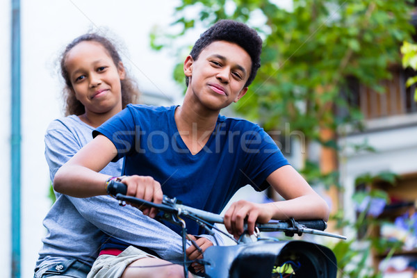 Stock photo: Smiling sister sitting with his brother riding an old bike